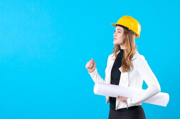 파란색에 계획을 들고 노란색 헬멧에 전면 보기 여성 건축가