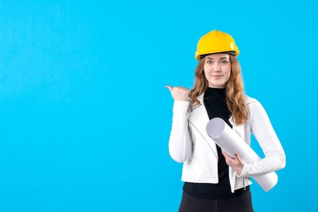 Вид спереди женский архитектор в желтом шлеме, держащий план на синем