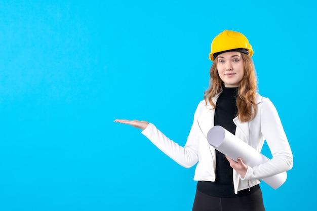 青の計画を保持している黄色のヘルメットの正面図の女性建築家