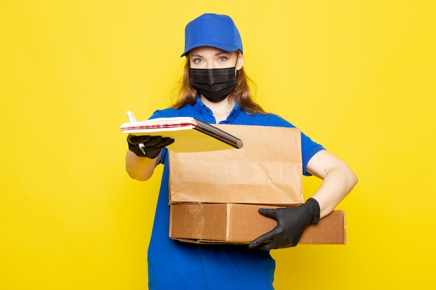 A front view female attractive courier in blue polo shirt blue cap and jeans holding package in black gloves black protective mask posing on the yellow background food service job
