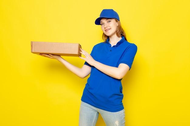 Un corriere attraente femminile di vista frontale in cappuccio blu della camicia di polo blu e jeans che sorridono pacchetto della tenuta sul lavoro giallo di servizio ristoro del fondo