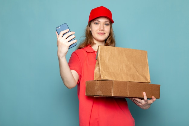 A front view female attractive courier in red polo shirt red cap holding brown package using her phone smiling on the blue background food service job