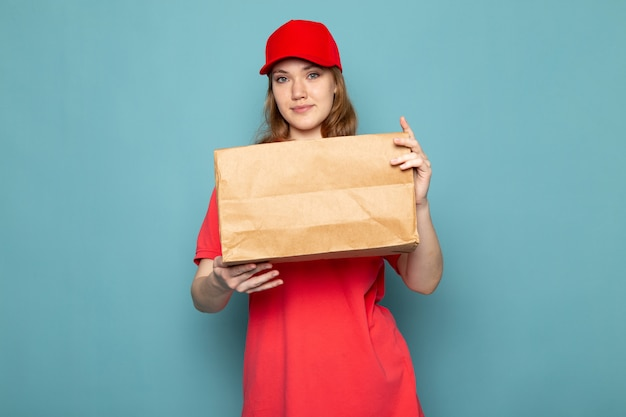 A front view female attractive courier in red polo shirt red cap and jeans holding package posing smiling on the blue background food service job