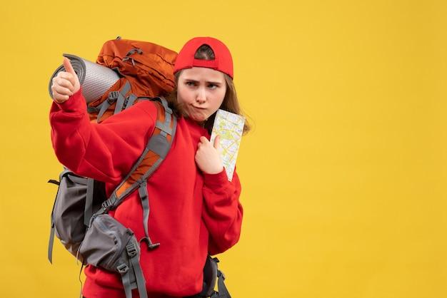 Женщина-туристка, вид спереди, держащая карту путешествий, показывает палец вверх