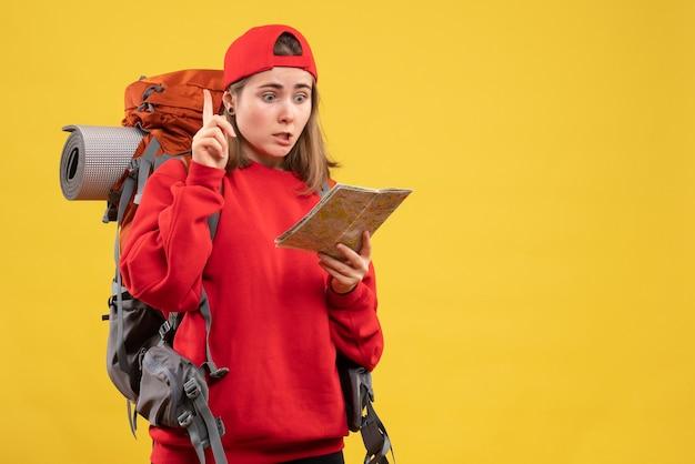 アイデアや質問で驚くべき旅行マップを保持している正面図の女性のバックパッカー