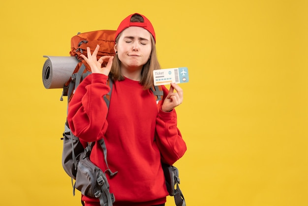 Okサインを作る旅行チケットを保持している正面図の女性のバックパッカー
