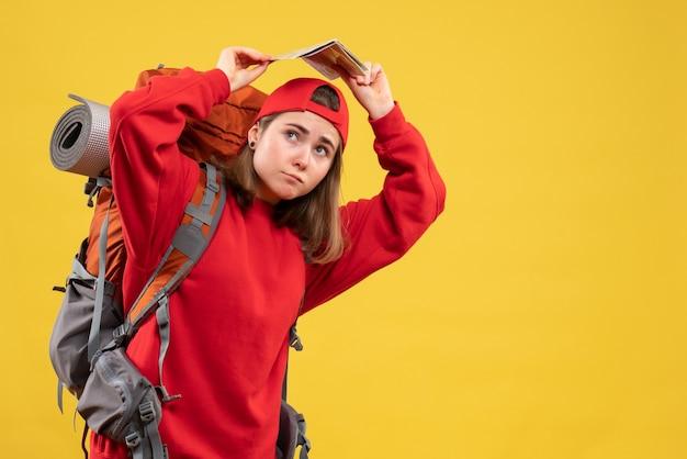 Женщина-туристка, вид спереди, подняв карту путешествия над головой
