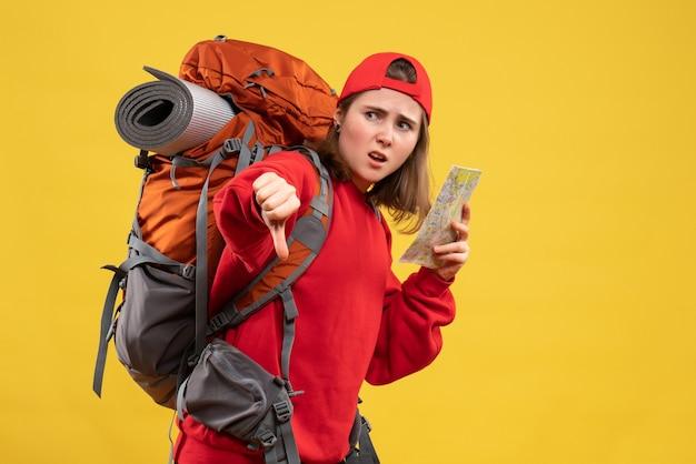 엄지 손가락을 아래로 만드는 여행지도를 들고 빨간 스웨터에 전면보기 여성 배낭