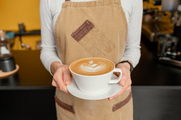 Front view of female barista holding decorated cup of coffee in hands