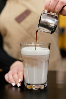 Front view of female barista pouring coffee in milk glass