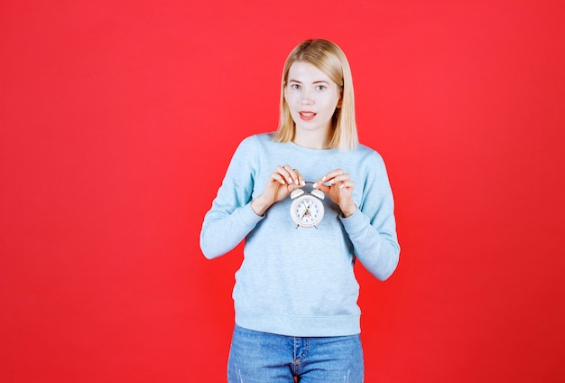 Front view of female blonde model who's holding te clock with her both hands and smiling while looking to her front side