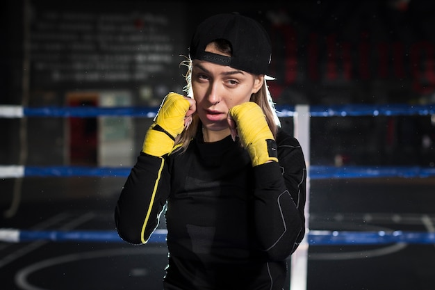 Front view of female boxer practicing in the ring with protective gloves