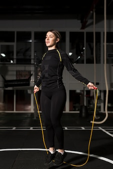 Front view of female boxer in working out apparel jumping rope