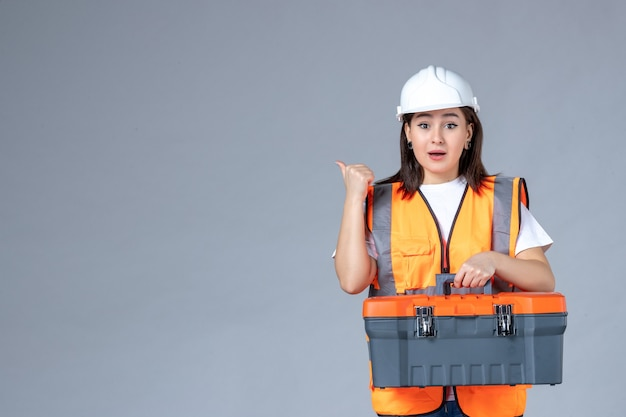 Front view of female builder carrying heavy tool case on white wall