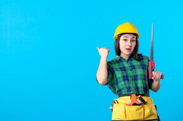 Costruttore femminile di vista frontale che tiene piccola sega sul lavoratore blu del costruttore del grattacielo di lavoro che costruisce