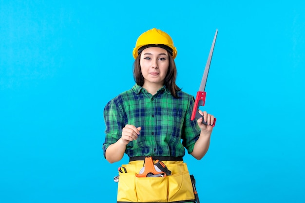 Front view female builder holding little saw on blue
