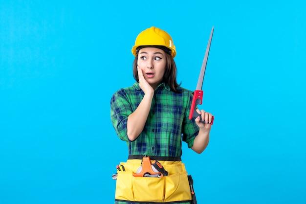 Costruttore femminile di vista frontale che tiene piccola sega sul blu