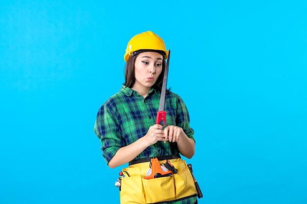 Женщина-строитель, вид спереди, держащая небольшую пилу на синем