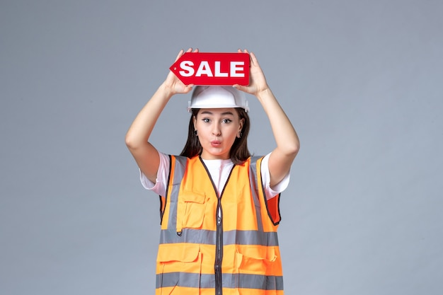 Front view of female builder holding red sale board on gray wall