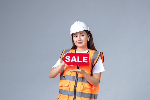 Front view of female builder holding red sale board on white wall