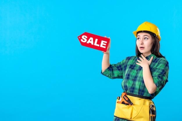 Costruttore femminile di vista frontale che tiene la scrittura rossa di vendita sul blu