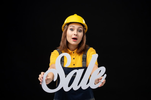 Front view female builder holding white sale sign on black wall