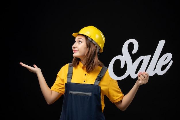 黒い壁に白い販売サインを保持している正面図の女性ビルダー