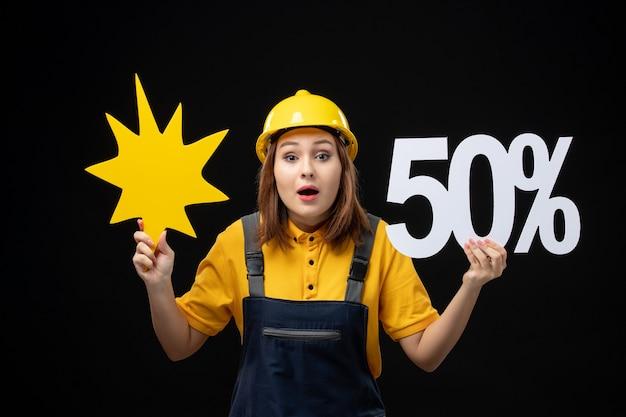 Женщина-строитель, вид спереди, держащая желтую фигуру и на черной стене