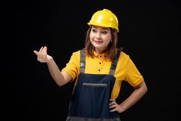 검은 벽에 누군가를 부르는 유니폼과 헬멧에 전면 보기 여성 빌더