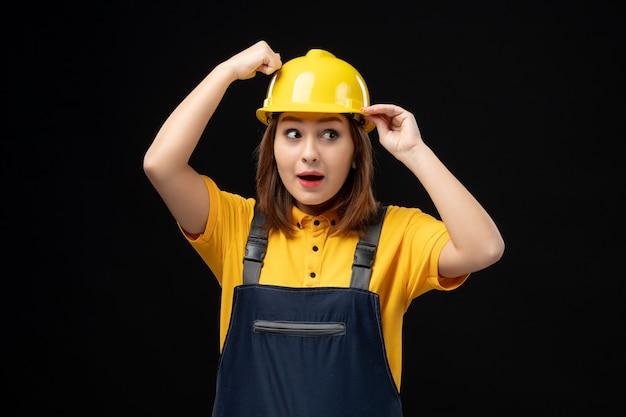 黒い壁に制服とヘルメットの正面図の女性ビルダー