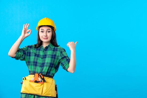 Вид спереди женщина-строитель в униформе и шлеме на синем