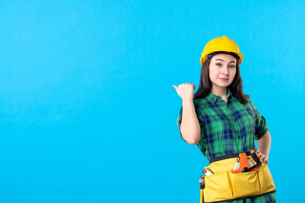 制服を着た正面図の女性ビルダーと青のヘルメット