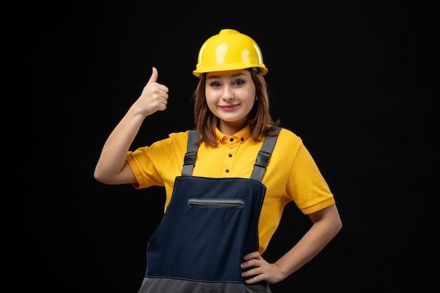 Вид спереди женщина-строитель в форме и шлеме на черной стене