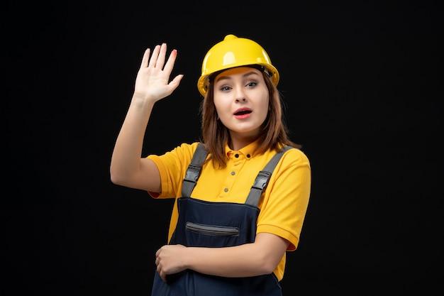 制服を着た正面図の女性ビルダーと黒い壁に手を振っているヘルメット