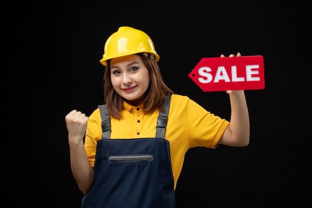 黒い壁に販売サインを保持している制服を着た女性ビルダーの正面図