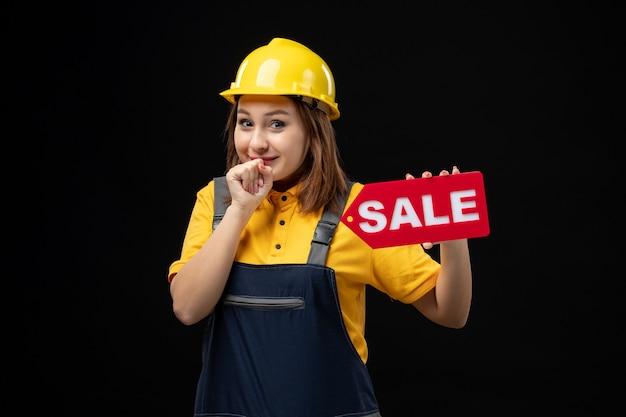 Вид спереди женщина-строитель в униформе держит знак продажи на черной стене