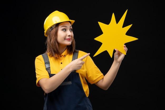 검은 벽에 노란색 그림을 들고 제복을 입은 전면 보기 여성 빌더
