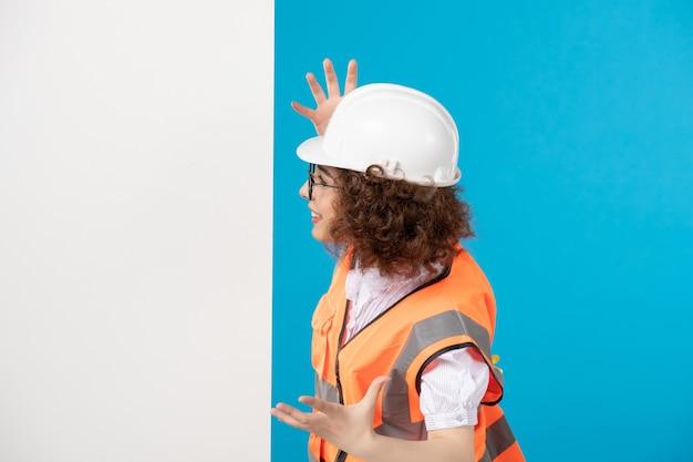 Женщина-строитель в униформе на синем, вид спереди
