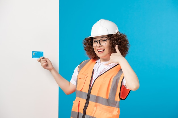 青いクレジットカードを手に青い制服を着た女性ビルダーの正面図