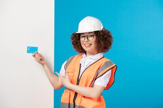 Вид спереди женщина-строитель в униформе с синей кредитной картой на синем