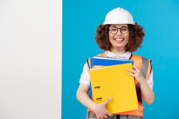 Вид спереди женщина-строитель в униформе с документами на синем