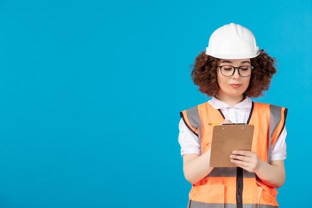 青に均一なメモを書く制服を着た正面図の女性ビルダー