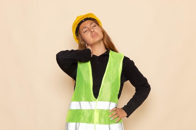 白い壁に首の痛みを持ってポーズをとって黄色いヘルメットの黒いシャツの正面図の女性ビルダー