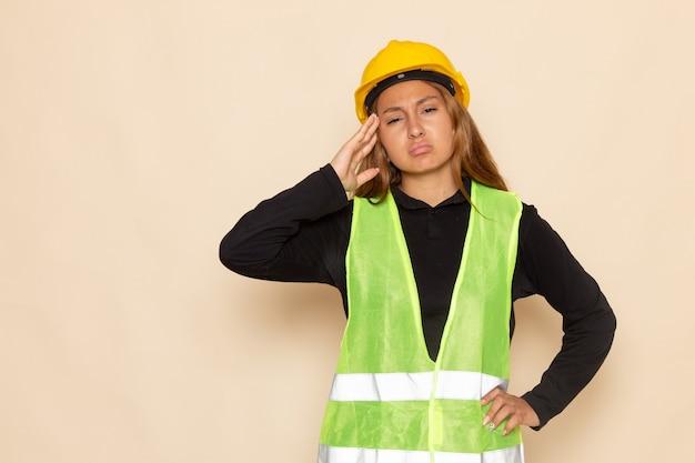 白い壁に思考をポーズ黄色いヘルメット黒シャツの正面図女性ビルダー