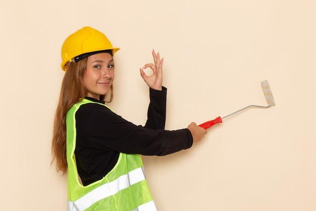 白い壁に絵画の壁を笑顔の黄色いヘルメット黒シャツの正面図女性ビルダー