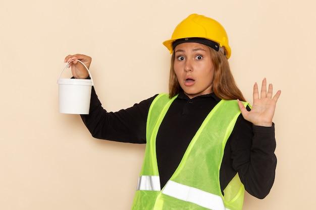 白い壁にペンキを保持している黄色いヘルメットの正面図女性ビルダー女性ビルダー建設建築家