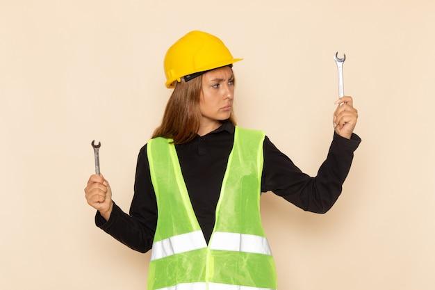 白い机の上に銀の楽器を保持している黄色いヘルメットの正面図女性ビルダー女性ビルダー建設建築家