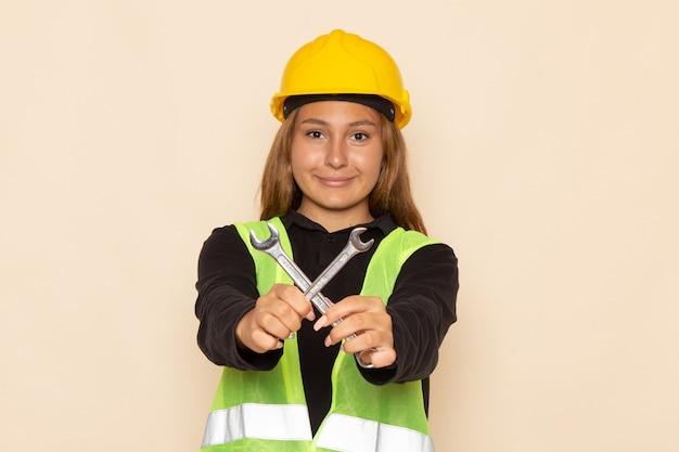 Вид спереди женщина-строитель в желтом шлеме, держащая серебряные инструменты на белой стене, женщина-строитель, строительный архитектор