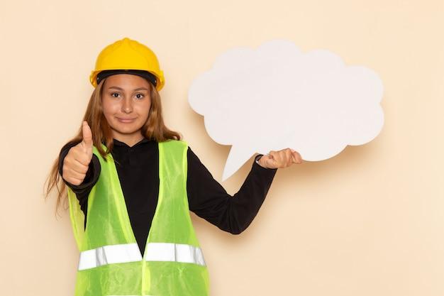 白い看板を保持し、白い壁に笑みを浮かべて黄色いヘルメットの正面図女性ビルダー建設