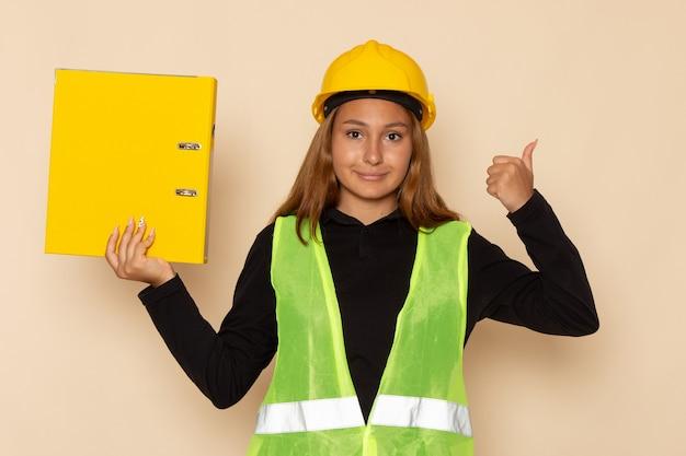 白い壁に笑みを浮かべて黄色のドキュメントを保持している黄色いヘルメットの正面図女性ビルダー